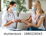 Small photo of Medical help at home. Woman doctor in a medical mask measures the patient's pulse and oxygen saturation to middle aged woman using a pulse oximeter while sitting on sofa, healthcare concept