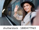 Pretty girl tourist takes selfie at the railway station against the background of the locomotive. Girl talking on video call  - stock photo