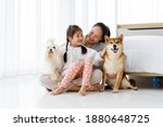 Small photo of Happy Asian mother and daughter sitting on bedroom floor with Maltese and Shiba Inu.