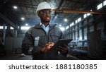 Small photo of Professional Heavy Industry Engineer Worker Wearing Safety Uniform and Hard Hat Uses Tablet Computer. Smiling African American Industrial Specialist Walking in a Metal Construction Manufacture.