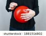 Small photo of Conceptual photography. The woman holds a red ball near his belly, which symbolizes bloating and flatulence. Then she brings a needle to it to burst the balloon and thus get rid of the problem.