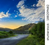 asphalt road going to mountain, passes rural places - stock photo