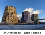 Small photo of Old destroyed cooling tower and two operating cooling towers. An unfinished cooling tower next to two completed ones. Cooling towers let off steam against the blue sky. Industrial landscape.