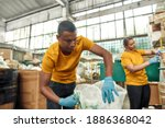 Small photo of Selective focus on young african american man working beside caucasian girl during putting used disposable cups into rubbish pressing machine on waste station. Garbage sorting and recycling concept