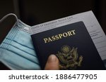 Small photo of Blurred COVID-19 Vaccination Record card, Passport of USA and Medical Mask. Immune passport or certificate for travel concept.