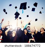 Small photo of Cheerful students throwing graduation caps in the Air