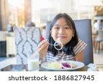 happy little girl eat onion in...
