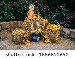 A Scarecrow Sitting On A Haybal ...