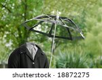 invisible man out for a walk in the rain with a useless umbrella - stock photo