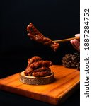 Small photo of phoenix claw dim sum on a wooden plate in a dark background. take the phoenix claw dim sum with chopsticks