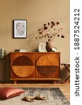 Small photo of Stylish interior with design wooden commode, stool, dried flowers in vase, unique decoration, carpet, mock up poster frame and elegant personal accessories. Modern living room in classic house.
