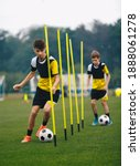 Small photo of Young Football Players Running Slalom and Dribbling With Balls Between Training Poles. Soccer Practice for Teenage Boys. Junior Level Soccer Team Traing Unit