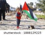 A Child Holds A Palestinian...