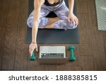 Young woman on yoga mat taking...