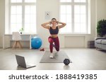 Small photo of Smiling athletic young woman training legs at home watching active sports workout video lesson. Fit female athlete in activewear doing forward lunges exercise with elastic resistance rubber glute band