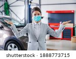Small photo of Smiling, friendly female car seller with face mask standing in garage of car salon and showing around garage. Car is all set and repaired.