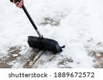 Woman Cleaning Snow From...