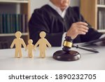 Small photo of Gavel, sound block and small wooden figurines of husband, wife and kid on judge's table in courthouse during court hearing. Family law, divorce lawyer, joint custody of child and alimony concept