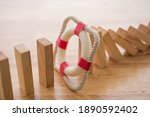 Small photo of Lifebuoy stop wood block fall domino effect on office wooden table background. Life, health and property insurance business concept. Insurance is risk control management.