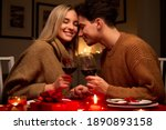 Small photo of Happy young couple in love clinking glasses drinking wine having romantic dinner date celebrating Valentines Day evening anniversary sitting at table at home or in restaurant. Valentine's Day concept
