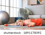 Small photo of Exhausted woman with excess weight lying on floor after training at home