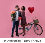 Small photo of Full length portrait of beautiful black couple with roses, Valentine's gift and bike kissing on pink studio background. Affectionate African American woman and her boyfriend going for ride together