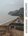 Small photo of Eype Beach, UK - July 25, 2020: People on a coastal walk, Thorncombe Beacon hill and Eype Beach, a secluded and unspoiled beach on Dorset's Jurassic Coast, on the background.
