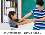 Small photo of Asian school boy extort, bullying, weak friend on blackboard in classroom background with angry face.Bully and physical abuse of children and kid student concept.