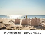 Small photo of close-up of small sandcastles topped with seaweed against a blue sky