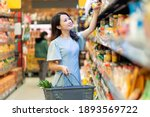 Small photo of Young girl is choosing to buy foodstuffs at the supermarket