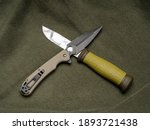 Small photo of Pocket knife and fixed blade knife on a green olive background