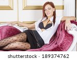 young sexy girl sitting on sofa | Shutterstock . vector #189374762