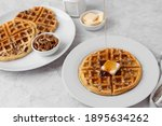 Small photo of Homemade Pecan Waffles on a White Plate with a Small Dish of Pecans; One Pecan Waffle on a White Plate with Butter and Maple Syrup; Butter and Maple Syrup in Background