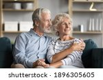 Small photo of Dreamy middle aged senior loving retired family couple looking in distance, planning common future or recollecting memories, enjoying peaceful moment relaxing together on cozy sofa in living room.