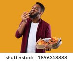 Small photo of Happy African Young Man Enjoying Pizza Biting Tasty Slice Posing With Box Over Yellow Background. Junk Food Lover Eating Italian Pizza In Studio. Unhealthy Male Nutrition And Cheat Meal