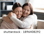 Small photo of Close up smiling grownup daughter and mature mother cuddling, enjoying tender moment, hugging, expressing love, having fun, sitting on cozy couch at home, family spending leisure time together