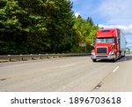 Small photo of Red big rig industrial grade bonnet long hauler diesel semi truck with high roof cab and refrigerator semi trailer running with commercial cargo on the wide highway road with green trees hillside