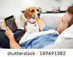 Stock photo young man with dog sit on sofa using digital tablet 189691382