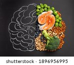 Small photo of Chalk hand drawn brain with assorted food, food for brain health and good memory: fresh salmon fish, green vegetables, nuts, berries on black background. Foods to boost brain power, top view