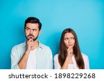 Small photo of Photo of pensive hesitant man and woman look empty space hand chin wear shirt isolated on blue color background