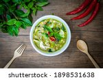 Small photo of Vegetarian Thai Green Curry in bowl at wood slate background. Veg Green Thai Curry is thailand cuisine dish with green chillies paste, basil, spices and vegetables. Thai Food top view