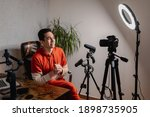Small photo of Young man sitting at the desk talking to the camera. Guy recording a video with professional equipments. Vlog, free lancer concept.