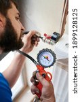 Small photo of Close up of bearded man filling pipes with pressurized air to inspect for leaks in new installation. Worker using manometer, checking gas tightness of heating system. Concept of gas tightness testing.