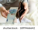 Small photo of Close up male hands with empty wallet taking out last cash money euros. Man holding currency remains and purse. Bankruptcy economic financial, income decline, poverty, unemployment concept, top view.