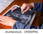 Kid drawing rocket on a blackboard - stock photo