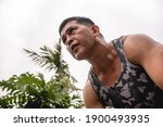 Small photo of A fit and determined 50 year old asian man in a tank top and an intense ruthless look during a workout. Looking forward while exercising