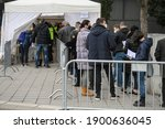 People Stand In Long Queues On...