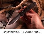 Small photo of Black pocket knife in hand. Automatic folding knife. Top.