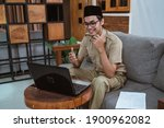 Small photo of male teacher in civil servant uniform with hand gestures during online meeting using a laptop computer when working from home