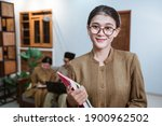 Small photo of female teacher in civil servant uniform wearing glasses smiling while carrying a book with the background of a team of teachers while working from home